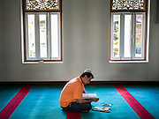10 JULY 2015 - BANGKOK, THAILAND: A man prays before Iftar at Haroon Mosque in Bangkok. Iftar is the evening meal when Muslims end their daily Ramadan fast at sunset. Iftar is a communal event at Haroon Mosque and hundreds of people usually attend the meal.     PHOTO BY JACK KURTZ