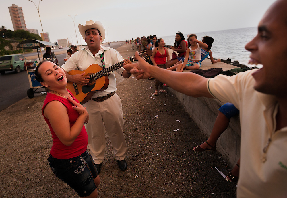 Young adults sing and dance to a street performer's music on the Malecon, a seawall stretching along the northern edge of Havana.
