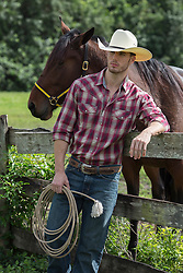 cowboy leaning against a fence with a horse standing nearby