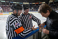 KELOWNA, BC - JANUARY 4:  Kelowna Rockets' athletic therapist tapes a cut on linesman Dustin Minty with referee Chris Crich at the boards during third period against the Vancouver Giants at Prospera Place on January 4, 2020 in Kelowna, Canada. (Photo by Marissa Baecker/Shoot the Breeze)