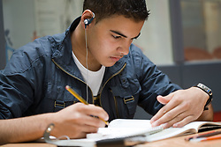 Post 16 student listening to music whilst doing art research,