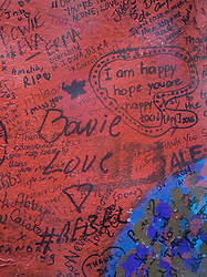 © Licensed to London News Pictures. 10/01/2017. London, UK. Messages are written on a mural and shrine to David Bowie in Brixton on the first anniversary of his death. David Bowie was born in Brixton, south London. Photo credit: Peter Macdiarmid/LNP