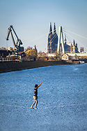 man on a slackline in the Rhine harbor in the district Deutz, in the background the cathedral and Severins bridge, Cologne, Germany.<br /> <br /> Mann auf einer Slackline im Deutzer Hafen am Rhein, im Hintergrund der Dom und Severinsbruecke, Koeln, Deutschland.