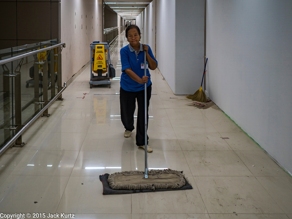 """24 DECEMBER 2015 - BANGKOK, THAILAND:  A worker cleans the floors in a not yet finished hallway in the new domestic terminal at Don Muang (also spelled Don Mueang) International Airport. The new terminal had its """"soft"""" opening Dec. 24. Don Muang is the airport used by low cost airlines serving Bangkok and is now the largest airport in the world for low cost carriers. In 2014, more than 21million passengers used Don Muang. Don Muang International Airport is the oldest airport in Asia and one of the oldest airports in the world. It started functioning as an airfield in 1914.    PHOTO BY JACK KURTZ"""