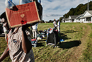 A man carries a box of goods while others look over the offerings of traveling salespersons. Four people, two men and two women, stopped by the temporary homes of Jamaican workers and showed articles of clothing, shoes and other items.