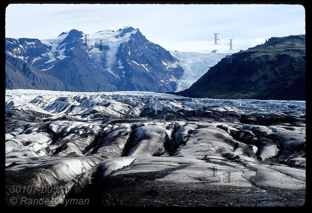 Black, silty foot of Svinafellsjokull frames distant Vatnajokull, third largest ice cap in world, near Skaftafell NP; Iceland.