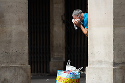 A men clean his face with a tissue on Rivoli Street in Paris on May 4, 2020, on the forty-ninth day of a strict lockdown in France, in place to attempt to stop the spread of the new coronavirus (COVID-19). Photo by Raphael Lafargue/ABACAPRESS.COM