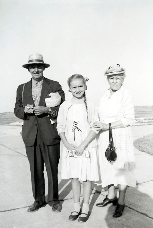 child with an TWA airplane ticket in her hand posing with her grandparents 1955