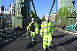 © Licensed to London News Pictures. 26/04/2020. London, UK. Council workers attempt to ease a congested bottleneck at Hammersmith bridge which sees large numbers of people making the most of the fine weather on a weekend where the public are urged to observe social distancing and only leave home where absolutely necessary. Photo credit: Guilhem Baker/LNP
