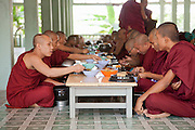 Monks sit for their only meal of the day at the Maha Gandaryon Monastery, near Mandaly, Myanmar