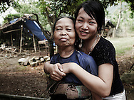 Family portraiture of an elderly ethnic woman with her granddaughter. The young girl hugs warmly the old woman. They look at the camera, smile and look happy. Pu Luong area, Hoa Binh province, Vietnam, Asia.