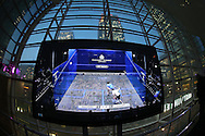 a view of the large screen showing a  BT Sport broadcasting the Wildcard Challenge match between Josh Masters of England (wearing Blue Shirt) vs Lyell Fuller of England (wearing the White shirt) with Canary Wharf as the back drop, before the main Final. Canary Wharf Squash Classic 2016 , at the East Wintergarden in Canary Wharf , London on Friday 11th March 2016.<br /> pic by John Patrick Fletcher, Andrew Orchard sports photography.