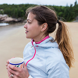 A woman drinking coffee on a cloudy morning at Sand Beach in Maine's Acadia National Park.