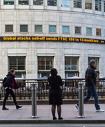 Workers pass the ticker at Canary Wharf telling them FTSE 100 stocks have plummeted to a 13 month low as European markets follow US and Asian markets lower on Tuesday as investors continued to dump shares. London, February 06 2018.