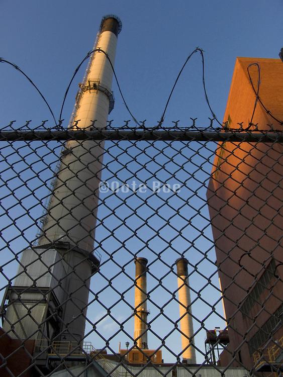 upward view of smoke stacks behind razor wire fence