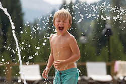 little boy enjoying the water from a public fountain