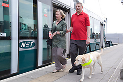 Vision impaired man with sighted guide and guide dog walking along the platform at the tram stop,