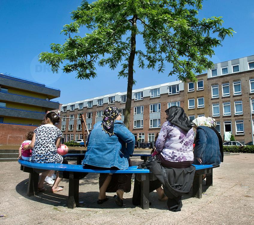 Nederland Rotterdam 24-05-2009 20090524 Foto: David Rozing .                                                                                    .Achterstandswijk Bloemhof, groepje moslima's zitten op pleintje op bankje onder boom Muslim woman chatting outside in neighbourhoud, muslims, straatbeeld, stadbeeld.Foto: David Rozing/