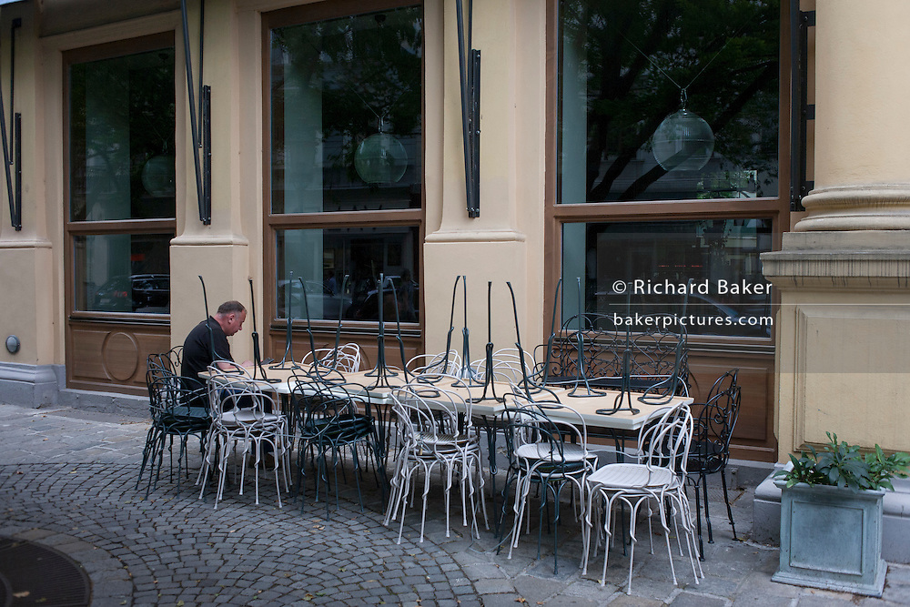 Man sitting at table with upturned cafe chairs in Vienna, Austria, EU.
