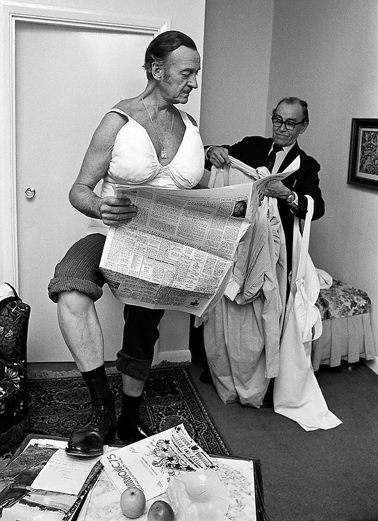 """British actor David Niven seen being dressed into costume in his dressing room at Pinewood Film Studio, UK during the filming of the movie """"Candleshoe"""" in 1976. Photographed by Terry Fincher"""