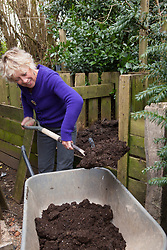 Carol Klein loading a wheelbarrow with compost from her compost heap