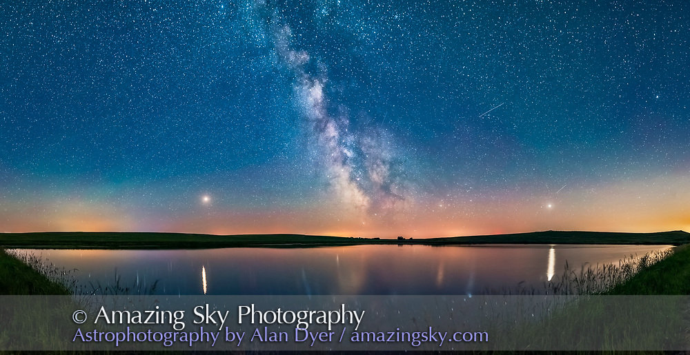 A 160° panorama taken July 5/6 of the summer Milky Way and the array of summer 2018 planets over the prairie pond near home in southern Alberta. <br /> <br /> Mars is bright to the left, Saturn is dimmer and at centre in the Milky Way, while bright Jupiter is at right. Mars and Jupiter nicely flank the Milky Way, and cast glitter paths on the water. The arcing line joining the planets defines the arc of the ecliptic, always low in the south in northern hemisphere summer. Mars was approaching Earth and brightening at this time heading for a late July opposition.<br /> <br /> The sky is deep blue with solstice twilight. Several satellite trails punctuate the sky. <br /> <br /> This is a panorama with 2 tiers of 6 segments each, stitched with Adobe Camera Raw. Each segment was 20 seconds at f/2 with the 20mm Sigma Art lens and Nikon D750 at ISO 6400.<br /> <br /> Glow effect and vignetting added with Zone System Express extension effects.