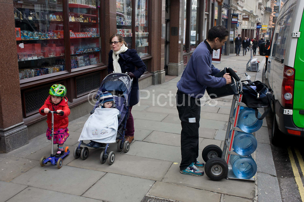 A mother and her children pass a delivery man and bottles of office drinking water in City street. As the mum hurries up the street, only her own agenda and destination is of concern. Her little girl concentrates on scooting along but a little boy tucked up under blankets in his buggy, looks over to the man who is about wheel his trolley to a nearby corporate building. There is a visual theme of wheels and circles in this scene: From the scooter to the buggy and bottles stacked on the trolley.