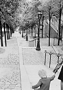 Down view, black and white photo of the Stairs in Montmartre, Paris, France with child holding a parent's hand. Also known as the Escaliers de Montmartre