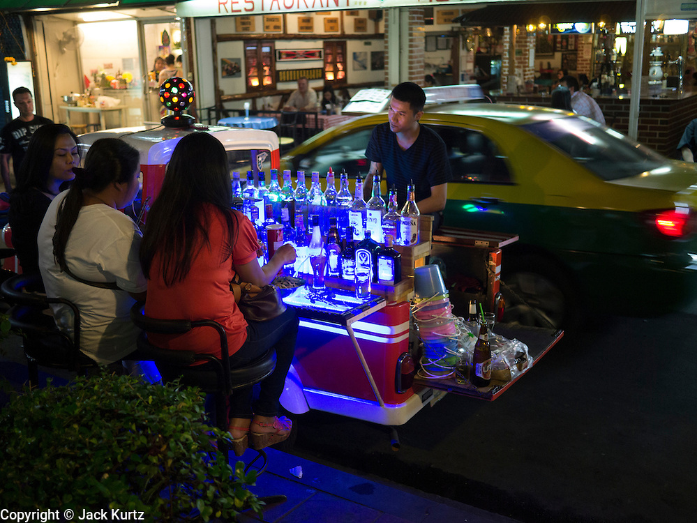 "05 JANUARY 2012 - BANGKOK, THAILAND:  People drink at a portable bar in a red light district off of Sukhumvit Road in Bangkok. Prostitution in Thailand is technically illegal, although in practice it is tolerated and partly regulated. Prostitution is practiced openly throughout the country. The number of prostitutes is difficult to determine, estimates vary widely. Since the Vietnam War, Thailand has gained international notoriety among travelers from many countries as a sex tourism destination. One estimate published in 2003 placed the trade at US$ 4.3 billion per year or about three percent of the Thai economy. It has been suggested that at least 10% of tourist dollars may be spent on the sex trade. According to a 2001 report by the World Health Organisation: ""There are between 150,000 and 200,000 sex workers (in Thailand).""      PHOTO BY JACK KURTZ"