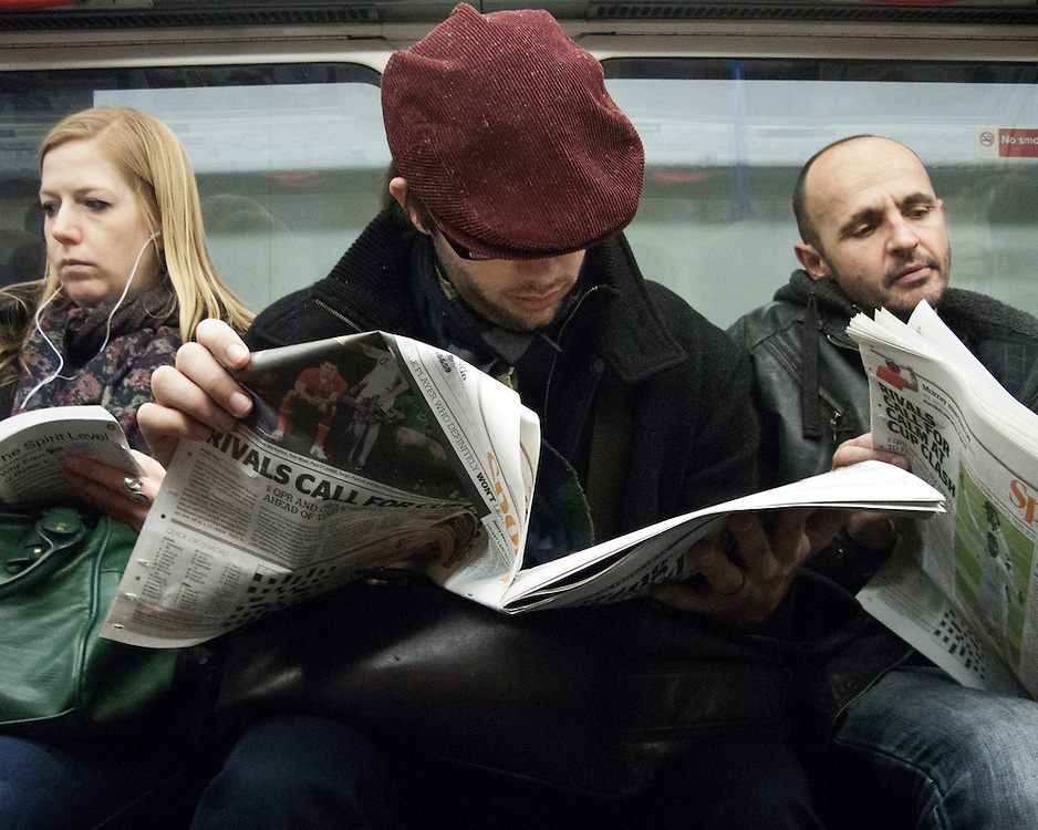 Portrait of a man reading a newspaper on the London Underground