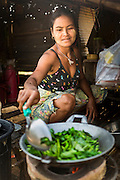 """01 MARCH 2014 - MAE SOT, TAK, THAILAND: A Burmese woman stir fries vegetables for her family in her home in a Burmese community in the forest a few kilometers north of Mae Sot. Mae Sot, on the Thai-Myanmer (Burma) border, has a very large population of Burmese migrants. Some are refugees who left Myanmar to escape civil unrest and political persecution, others are """"economic refugees"""" who came to Thailand looking for work and better opportunities.    PHOTO BY JACK KURTZ"""