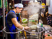 """18 MAY 2017 - BANGKOK, THAILAND:  A chef makes noodle soups for customers at a street food stall in Bangkok's Chinatown. City officials in Bangkok have taken steps to rein in street food vendors. The steps were originally reported as a """"ban"""" on street food, but after an uproar in local and international news outlets, city officials said street food vendors wouldn't be banned but would be regulated, undergo health inspections and be restricted to certain hours on major streets. On Yaowarat Road, in the heart of Bangkok's touristy Chinatown, the city has closed some traffic lanes to facilitate the vendors. But in other parts of the city, the vendors have been moved off of major streets and sidewalks.     PHOTO BY JACK KURTZ"""