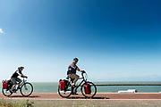 Fietsers rijden over de Brouwersdam. De dam is het zevende bouwwerk van de Deltawerken en vormt de afscheiding van het Grevelingenmeer met de Noordzee. Halverwege de dam vindt veel recreatie plaats met kitesurfers aan de zeekant en vakantieparken met jachthavens aan de kant van het meer.<br /> <br /> Cyclists ride over the Brouwersdam. The dam is the seventh structure of the Delta Works and forms the separation of the Grevelingenmeer with the North Sea. Halfway through the dam there is a lot of recreation with kite surfers on the sea side and holiday parks with marinas on the side of the lake.