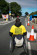 A wheel chair bound anti-fracking activist near the entrance to Quadrillas drill site in New Preston Road , July 01 2017, Lancashire, United Kingdom. The t-shirt says:  The Desolate North which  is how Lord Howell described Lancashire.  The blockade is a repsonse to the emmidiate drilling for shale gas, fracking, by the fracking company Quadrilla and part of an ongoing struggle where makeshift towers and makeshift camps have sprung up outside the premisses. Lancashire voted against permitting fracking but was over ruled by the conservative central Government.  Fracking is a highly contested way of extracting gas, it is risky to extract and damaging to the environment and is banned in parts of Europe . Lancashire has in the past experienced earth quakes blamed on fracking.