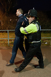 © under license to London News Pictures.  11/12/2010 A man is escorted away from the stadium after the Devon derby between Exeter and Plymouth today (Saturday). Large numbers of police were present after violence broke out at the last derby. Picture credit should read: David Hedges/LNP