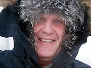 Strassen Portrait von einem Mann mit Kopfbedeckung geschützt gegen die extreme Kaelte in der Innenstadt von Jakutsk. Jakutsk wurde 1632 gegruendet und feierte 2007 sein 375 jaehriges Bestehen. Jakutsk ist im Winter eine der kaeltesten Grossstaedte weltweit mit durchschnittlichen Winter Temperaturen von -40.9 Grad Celsius. Die Stadt ist nicht weit entfernt von Oimjakon, dem Kaeltepol der bewohnten Gebiete der Erde.<br /> <br /> Street portrait of a man protected with headgears against the extrem climate  in the city center of Yakutsk. Yakutsk was founded in 1632 and celebrated 2007 the 375th anniversary - billboard announcing the celebration. Yakutsk is a city in the Russian Far East, located about 4 degrees (450 km) below the Arctic Circle. It is the capital of the Sakha (Yakutia) Republic (formerly the Yakut Autonomous Soviet Socialist Republic), Russia and a major port on the Lena River. Yakutsk is one of the coldest cities on earth, with winter temperatures averaging -40.9 degrees Celsius.