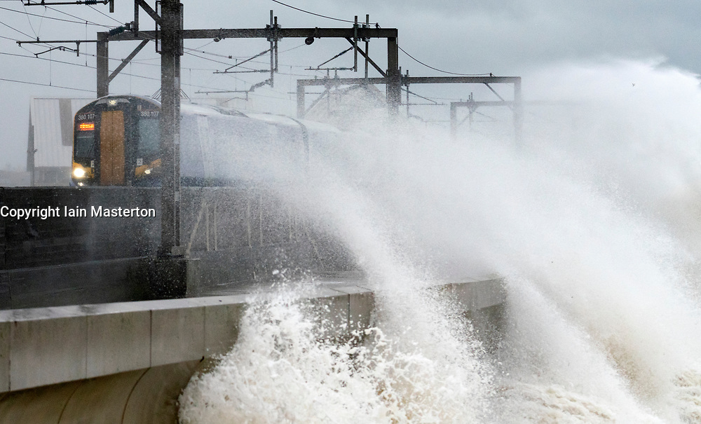 Saltcoats, Ayrshire,Scotland, UK. 13th Jan 2020. Huge waves crash against shore in Saltcoats during Storm Brendan. The storm affected the entire west coast of the UK and brought widespread travel disruption. Pictured. Scotrail train engulfed in luges waves, The train service was cancelled shortly afterwards. Iain Masterton/Alamy Live News