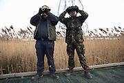 Camouflaged birdspotters peer through binoculars for wildlife at the RSPB's bird and wildlife reserve at Rainham Marshes, Essex