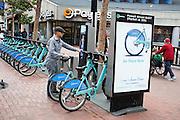 Een man brengt een fiets terug bij een station van Bay Area Bike Share, het deelfietssysteem in San Francisco. Het openbaar huursysteem is vanaf 2013 operatief in San Francisco en bestaat momenteel uit ongeveer 700 fietsen verdeeld over 70 geautomatiseerde stations. De fietsen kunnen bij elk station worden gepakt en op een willekeurig ander station worden neergezet. Per rit is het eerste half uur gratis, de huurfietsen zijn bedoeld voor korte ritten.<br /> <br /> A man returns a bike at a station of Bay Area Bike Share, the bike sharing system in San Francisco. The public rental system has been operative since 2013 in San Francisco and currently consists of about 700 bikes spread over 70 automated stations. The bikes can be picked up at each station and put down at any other station. Per trip, the first half hour is for free. The rental bicycles are provided for short journeys.
