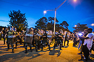 Police in riot gear clash with people protesting against the killing of Alton Sterling on July 10 , 2016.