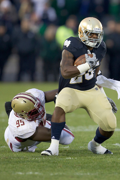 Notre Dame tailback Jonas Gray (#25) runs for yardage as Boston College defensive tackle Dominic Appiah (#95) attempts to make the tackle during first quarter of NCAA football game between Notre Dame and Boston College.  The Notre Dame Fighting Irish defeated the Boston College Eagles 16-14 in game at Notre Dame Stadium in South Bend, Indiana.