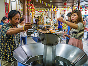 """12 OCTOBER 2012 - RAI KHRING, NAKHON PATHOM, THAILAND:  Thai Buddhists pour oil into a lamp to make merit at Wat Rai Khring in Nakhon Pathom province. Wat Rai Khring was built in 1791, the Abbot at the time, Somdej Phra Phuttha Chan (Pook), named this temple after the district. When construction was completed, the Buddha image was brought from another temple and enshrined here. Later locals named the image """"Luang Pho Wat Rai Khing"""". The Buddha image is of Chiang Saen style and is assumed to have been built by Lanna Thai and Lan Chang craftsmen.     PHOTO BY JACK KURTZ"""