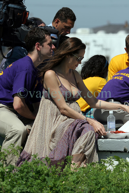 16 March 2008. New Orleans, Louisiana.<br /> A clearly pregnant Angelina Jolie poses with local residents in the Lower 9th Ward. She lets a young girl put her hands on her bump. She was in town for the 'Make a Difference, Make a Commitment' with Brad Pitt. Make it Right Foundation aided by the Clinton Global Initiative.<br /> Photo by:  Charlie Varley