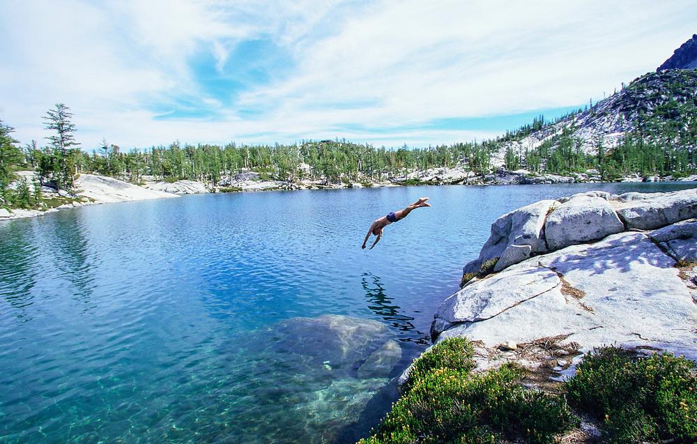 A man diving intoa mountain / alpine lake, Enchantment Lakes Wilderness, Washington Cascades, USA.