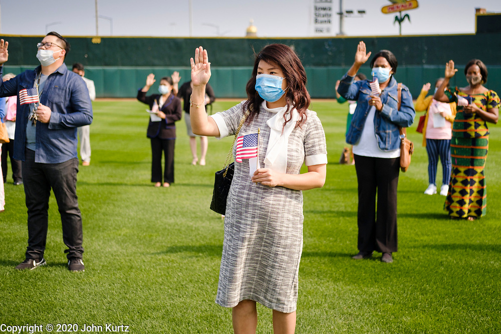 17 SEPTEMBER 2020 - DES MOINES, IOWA: People take the Oath of Allegiance during a naturalization ceremony at Principal Park, a minor league baseball stadium in downtown Des Moines. About 75 people from 32 countries were naturalized as US citizens Thursday. It was the last citizenship ceremony in Des Moines before citizenship fees dramatically increase. Starting Oct. 2, the fee to apply for U.S. citizenship will increase from $640 to $1,160 if filed online, or $ 1,170 in paper filing, a more than 80% increase in cost. Advocates for immigration are afraid the new fees will be too expensive for many immigrants and say it's an effort by the Trump Administration to limit the number of new citizens welcomed into the United States. Because of the COVID-19 pandemic, there has been dramatic slow down in the number of naturalization ceremonies this year.    PHOTO BY JACK KURTZ