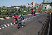 After being closed indefinitely to all traffic due to structural faults, kids cycle across Hammersmith Bridge, on 11th April 2019, in west London, England. Safety checks revealed critical faults and Hammersmith and Fulham Council has said its ben left with no choice but to shut the bridge until refurbishment costs could be met. The government has said that between 2015 and 2021 its is providing £11bn of support to the 132-year-old bridge.