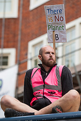 London, UK. 7 October, 2019. A climate activist from Extinction Rebellion sits on top of a large truck outside the Home Office on the first day of International Rebellion protests to demand a government declaration of a climate and ecological emergency, a commitment to halting biodiversity loss and net zero carbon emissions by 2025 and for the government to create and be led by the decisions of a Citizens' Assembly on climate and ecological justice.