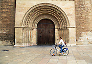 Woman cycling past arched doorway of the cathedral church building in city of Valencia, Spain