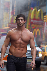 shirtless body builder walking in Times Square in the rain