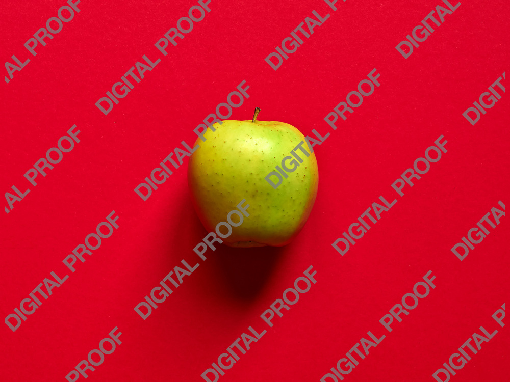 Above view of a Green apple isolated in a red background in studio
